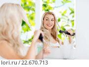 Купить «woman with styling iron doing her hair at bathroom», фото № 22670713, снято 13 февраля 2016 г. (c) Syda Productions / Фотобанк Лори
