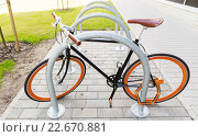 Купить «close up of bicycle locked at street parking», фото № 22670881, снято 30 мая 2015 г. (c) Syda Productions / Фотобанк Лори