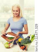 Купить «smiling woman cooking vegetable salad at home», фото № 22671329, снято 26 апреля 2015 г. (c) Syda Productions / Фотобанк Лори