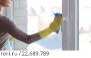 Купить «woman in gloves cleaning window with rag», видеоролик № 22689789, снято 16 апреля 2016 г. (c) Syda Productions / Фотобанк Лори