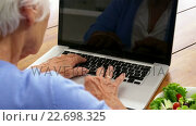 Купить «Close up mature woman using a laptop with a salad putting on the table», видеоролик № 22698325, снято 27 июня 2019 г. (c) Wavebreak Media / Фотобанк Лори