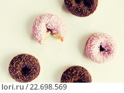 Купить «close up of glazed donuts pile over white», фото № 22698569, снято 21 мая 2015 г. (c) Syda Productions / Фотобанк Лори