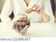 Купить «close up of hands with chocolate cookies in jar», фото № 22699657, снято 21 мая 2015 г. (c) Syda Productions / Фотобанк Лори