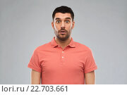 surprised man in polo t-shirt over gray background. Стоковое фото, фотограф Syda Productions / Фотобанк Лори