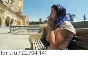 Купить «Девушка сидит на скамейке и молится», видеоролик № 22704141, снято 28 апреля 2016 г. (c) Потийко Сергей / Фотобанк Лори