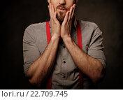 Купить «Young handsome man with beard wearing suspenders and posing on dark background.», фото № 22709745, снято 4 апреля 2016 г. (c) Andrejs Pidjass / Фотобанк Лори