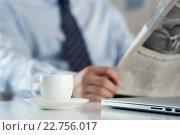 Купить «Белая чашка с блюдцем на столе на фоне бизнесмена, который читает газету», фото № 22756017, снято 6 апреля 2016 г. (c) Людмила Дутко / Фотобанк Лори