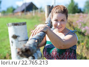 Купить «Attractive village woman in sundress posing near fence», фото № 22765213, снято 20 июля 2013 г. (c) Кекяляйнен Андрей / Фотобанк Лори