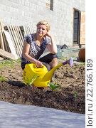 Купить «Улыбающаяся женщина с лейкой на дачном участке», фото № 22766189, снято 12 мая 2013 г. (c) Евгений Ткачёв / Фотобанк Лори
