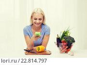 Купить «smiling woman with smartphone cooking vegetables», фото № 22814797, снято 26 апреля 2015 г. (c) Syda Productions / Фотобанк Лори