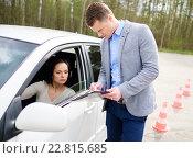 Купить «Driving instructor and woman student in examination area», фото № 22815685, снято 1 мая 2015 г. (c) Andrejs Pidjass / Фотобанк Лори