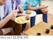 Купить «close up of friends eating fast food at home», фото № 22816141, снято 22 марта 2014 г. (c) Syda Productions / Фотобанк Лори