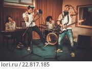Купить «Multiracial music band performing in a recording studio», фото № 22817185, снято 29 июля 2015 г. (c) Andrejs Pidjass / Фотобанк Лори