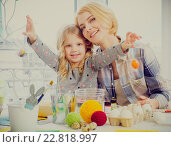 Купить «Cheerful mother and her daughter painting and decorating easter eggs.», фото № 22818997, снято 3 февраля 2016 г. (c) Andrejs Pidjass / Фотобанк Лори
