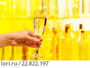 Купить «Рука с бокалом шампанского на желтом фоне», фото № 22822197, снято 10 января 2016 г. (c) Сергей Новиков / Фотобанк Лори
