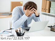 Купить «Офисный сотрудник перед ноутбуком держится за голову», фото № 22828197, снято 6 апреля 2016 г. (c) Людмила Дутко / Фотобанк Лори