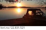 Купить «Яркое солнце над горизонтом, моторная лодка пришвартованная к причалу во время рассвета», видеоролик № 22831521, снято 11 мая 2016 г. (c) Кекяляйнен Андрей / Фотобанк Лори