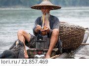 Старый рыбак закуривает трубку во время рыбалки традиционным для китая способом с помощью ручного баклана на фоне гор в провинции Гуанси (2013 год). Редакционное фото, фотограф Николай Винокуров / Фотобанк Лори