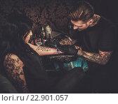 Купить «Professional tattoo artist makes a tattoo on a young girl's hand.», фото № 22901057, снято 8 мая 2016 г. (c) Andrejs Pidjass / Фотобанк Лори