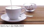 Купить «cream pouring to coffee cup on wooden table», видеоролик № 22926069, снято 15 апреля 2016 г. (c) Syda Productions / Фотобанк Лори