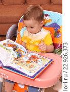 Купить «Маленький ребенок листает книгу сидя в кресле», фото № 22926373, снято 26 октября 2015 г. (c) Виктор Топорков / Фотобанк Лори