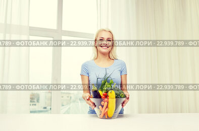 smiling young woman cooking vegetables at home