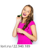 Купить «happy young woman or teen girl with party horn», фото № 22940189, снято 31 октября 2015 г. (c) Syda Productions / Фотобанк Лори