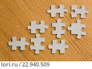 Купить «close up of puzzle pieces on wooden surface», фото № 22940509, снято 21 апреля 2016 г. (c) Syda Productions / Фотобанк Лори