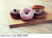 Купить «close up of glazed donuts pile on wooden table», фото № 22940585, снято 21 мая 2015 г. (c) Syda Productions / Фотобанк Лори