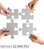 Купить «close up of hands connecting puzzle pieces», фото № 22940953, снято 21 апреля 2016 г. (c) Syda Productions / Фотобанк Лори
