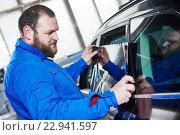 Купить «car tinting. Automobile mechanic technician applying foil», фото № 22941597, снято 14 апреля 2016 г. (c) Дмитрий Калиновский / Фотобанк Лори