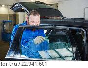 Купить «car tinting. Automobile mechanic technician applying foil», фото № 22941601, снято 14 апреля 2016 г. (c) Дмитрий Калиновский / Фотобанк Лори