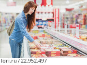 Купить «Customer picking a product in the frozen aisle», фото № 22952497, снято 15 октября 2015 г. (c) Wavebreak Media / Фотобанк Лори