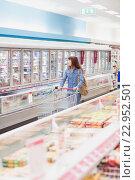 Купить «Customer looking for a product in the frozen aisle», фото № 22952501, снято 15 октября 2015 г. (c) Wavebreak Media / Фотобанк Лори