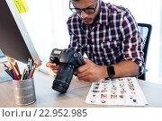 Купить «Side view of photographer working at desk», фото № 22952985, снято 20 марта 2016 г. (c) Wavebreak Media / Фотобанк Лори