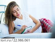 Купить «Portrait of girl putting dreams in notepad», фото № 22986061, снято 17 августа 2018 г. (c) Яков Филимонов / Фотобанк Лори