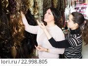 Купить «Two customers purchasing hair extension», фото № 22998805, снято 17 октября 2018 г. (c) Яков Филимонов / Фотобанк Лори