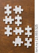 Купить «close up of puzzle pieces on wooden surface», фото № 23003525, снято 21 апреля 2016 г. (c) Syda Productions / Фотобанк Лори