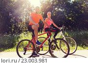 Купить «happy couple riding bicycle outdoors», фото № 23003981, снято 5 июля 2015 г. (c) Syda Productions / Фотобанк Лори