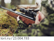 Купить «soldier or hunter shooting with gun in forest», фото № 23004193, снято 14 августа 2014 г. (c) Syda Productions / Фотобанк Лори