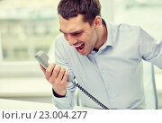 Купить «furious businessman calling on phone in office», фото № 23004277, снято 18 июня 2015 г. (c) Syda Productions / Фотобанк Лори