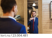 Купить «man trying tie on at mirror in clothing store», фото № 23004481, снято 1 апреля 2016 г. (c) Syda Productions / Фотобанк Лори