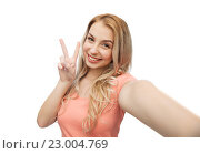 Купить «smiling woman taking selfie and showing peace sign», фото № 23004769, снято 30 апреля 2016 г. (c) Syda Productions / Фотобанк Лори
