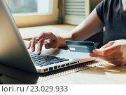 Купить «Руки с банковской картой над клавиатурой ноутбука», фото № 23029933, снято 3 мая 2016 г. (c) Константин Колосов / Фотобанк Лори