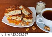 Купить «Домашний манный пирог с изюмом, яблоком и маком на столе с чашкой чая и баночкой кефира на полдник», фото № 23033337, снято 3 июня 2016 г. (c) Виктория Катьянова / Фотобанк Лори