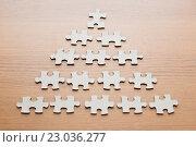 Купить «close up of puzzle pieces on wooden surface», фото № 23036277, снято 21 апреля 2016 г. (c) Syda Productions / Фотобанк Лори
