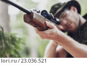 Купить «soldier or hunter shooting with gun in forest», фото № 23036521, снято 14 августа 2014 г. (c) Syda Productions / Фотобанк Лори