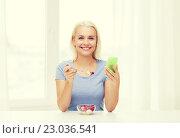 Купить «woman with smartphone eating fruits at home», фото № 23036541, снято 26 апреля 2015 г. (c) Syda Productions / Фотобанк Лори