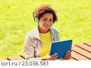 Купить «happy african woman with tablet pc and headphones», фото № 23036581, снято 4 июня 2015 г. (c) Syda Productions / Фотобанк Лори