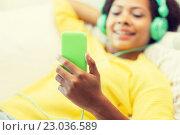 Купить «happy african woman with smartphone and headphones», фото № 23036589, снято 4 июня 2015 г. (c) Syda Productions / Фотобанк Лори